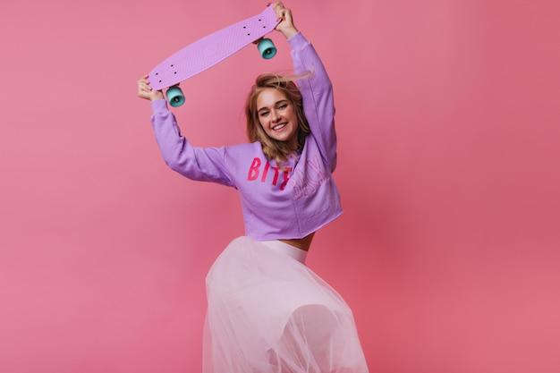 Blithesome weibliches modell im weißen rock, der mit glücklichem gesichtsausdruck tanzt. innenporträt des eleganten blonden mädchens mit skateboard.