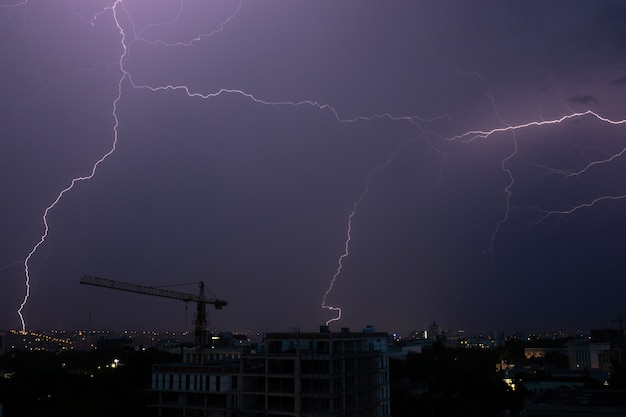 Blitz und gewitter über der stadt bei nacht auf dunklem himmelhintergrund.