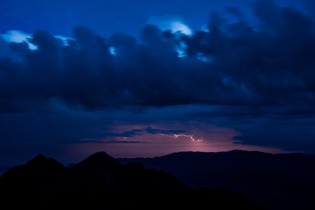 Blitz- und gewitterwolken in der nacht über bergen