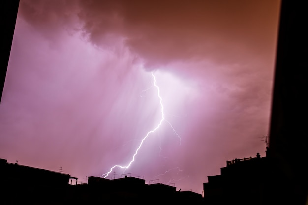 Blitzschlag, der auf eine stürmische nacht in der stadt fällt.