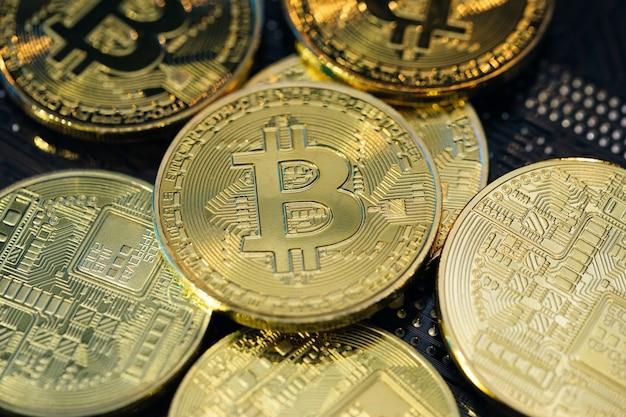 Blockchain-technologie, bitcoin-mining-konzept. viel bitcoin crypto währung bitcoin btc bit coin. nahaufnahme schuss von bitcoin-münzen lokalisiert auf motherboard-hintergrund.