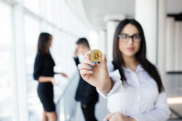 Blockchain- und investitionskonzept. geschäftsfrauführerin, die bitcoin vor dem besprechen des teams im amt hält.