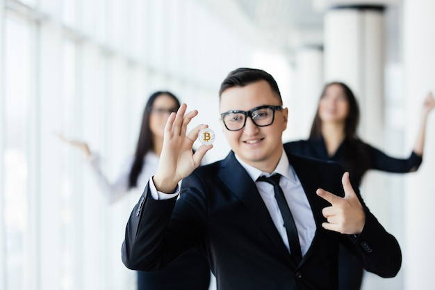 Blockchain- und investitionskonzept. geschäftsmannführer, der bitcoin hält und auf münze vor seinem team im amt zeigt.