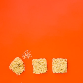 Blöcke der sofortigen nudeln ordneten auf heller orange oberfläche an