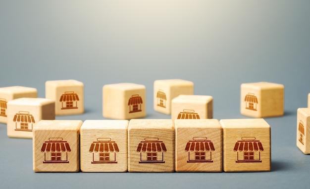 Blöcke, die einkaufsläden symbolisieren. aufbau eines erfolgreichen geschäftsimperiums. franchise-konzept