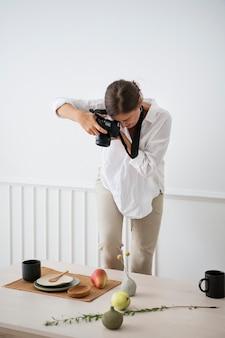 Blogger beim fotografieren des tellerdekors auf dem esstisch