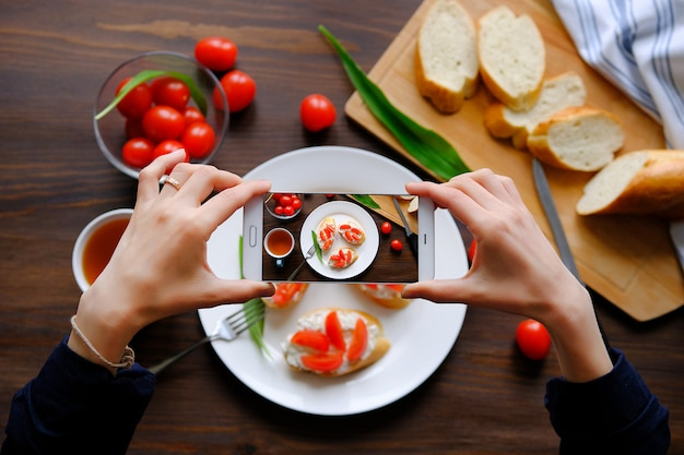 Blogger fotografieren das frühstück mit ihrem smartphone