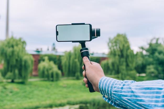 Blogger in der natur nimmt videos auf einem smartphone auf