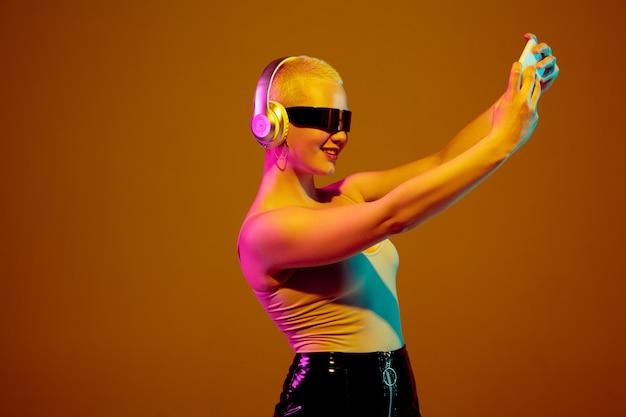 Blogger. junge kaukasische frau auf brauner studiooberfläche im neonlicht. schönes weibliches model mit modischer, trendiger brille. menschliche emotionen, gesichtsausdruck, verkauf, anzeigenkonzept. freaks kultur.