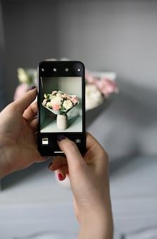 Blogger macht ein foto von einem blumenstrauß