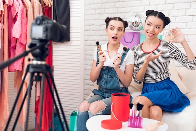 Blogger-mädchen halten pinsel und parfüm in die kamera.