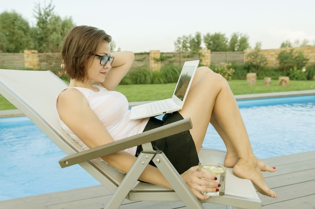 Blogger mit laptop in der nähe des pools