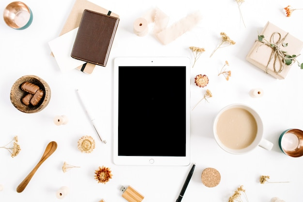 Blogger- oder freiberufler-arbeitsplatz mit tablet, kaffeetasse, notizbuch, süßigkeiten und zubehör auf weißem hintergrund. flacher, minimalistischer, brauner home-office-schreibtisch mit draufsicht. beauty-blog-konzept.