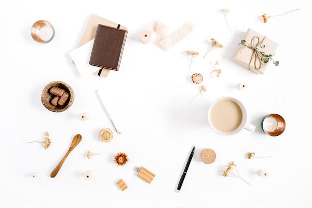 Blogger- oder freiberufler-arbeitsplatzrahmen aus kaffeetasse, notizbuch, süßigkeiten und zubehör auf weißem hintergrund. flacher, minimalistischer, brauner home-office-schreibtisch mit draufsicht. beauty-blog-konzept.
