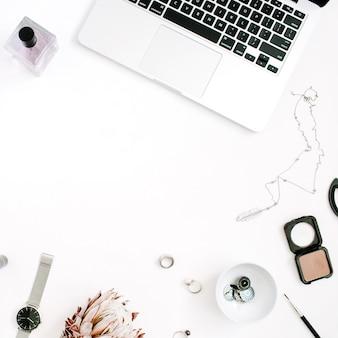Blogger- oder freiberufler-rahmenarbeitsplatz mit laptop-protea-blumennotizbuch und femininem zubehör auf weißem hintergrund flacher draufsicht-home-office-schreibtisch