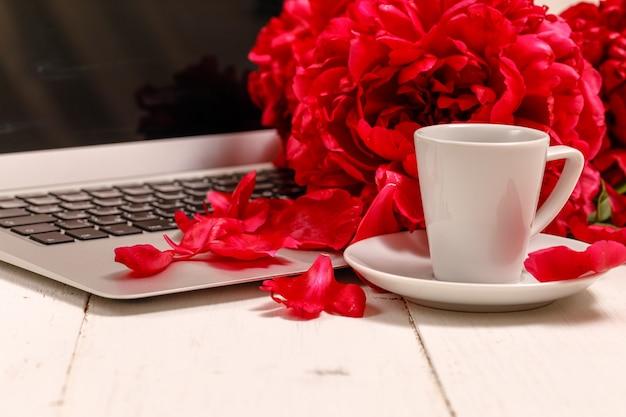 Blogger- oder freiberuflerarbeitsbereich mit einem notizbuch, einer tastatur, roten pfingstrosen auf einem weißen hintergrund