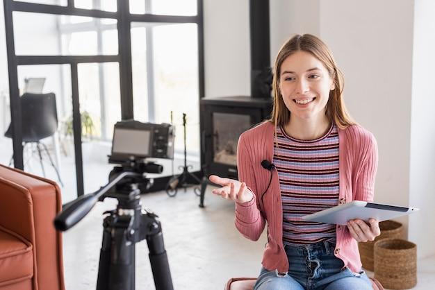 Blogger spricht mit der kamera und benutzt das tablet