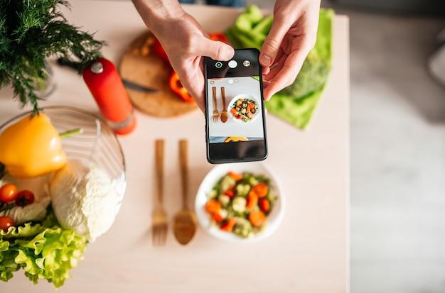 Blogger-typ, der fotos von salat in der küche macht