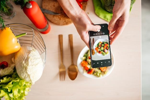 Blogger-typ fotografiert salat in der küche