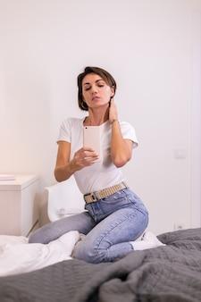 Blogger zu hause in freizeitkleidung gemütliches schlafzimmer macht foto selfie auf handy im spiegel