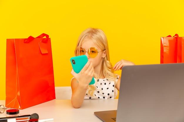Bloggerin des kleinen mädchens mit dem blauen telefon, das video für blog und anhänger macht, die im gelben studio isoliert sitzen.