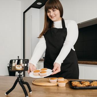 Bloggerin, die sich beim zubereiten von muffins aufzeichnet