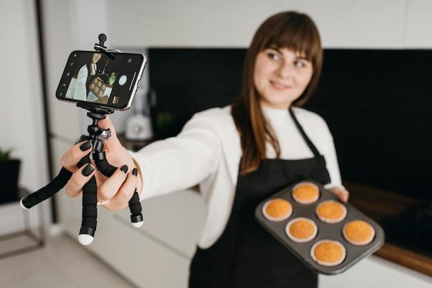 Bloggerin, die sich mit dem smartphone aufzeichnet, während sie muffins vorbereitet
