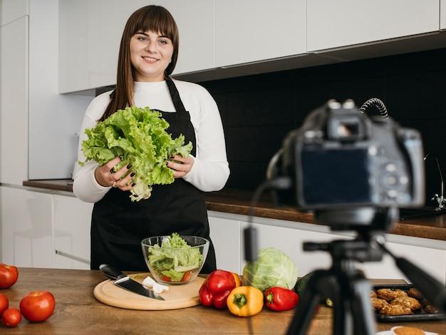 Bloggerin, die sich mit der kamera aufzeichnet, während salat vorbereitet