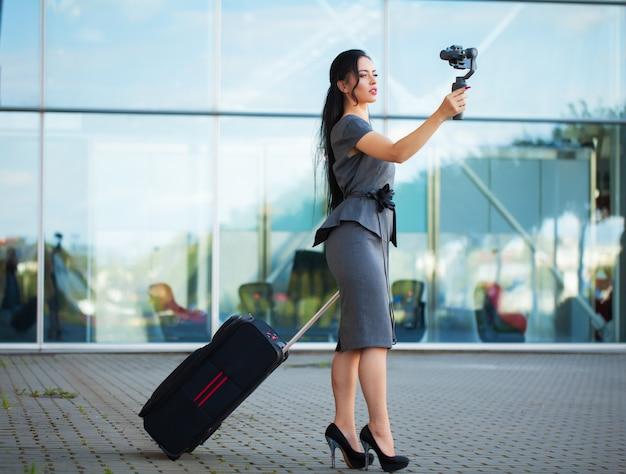 Bloggerin dreht ein video über das reisen mit einem elektronischen stabilisator.