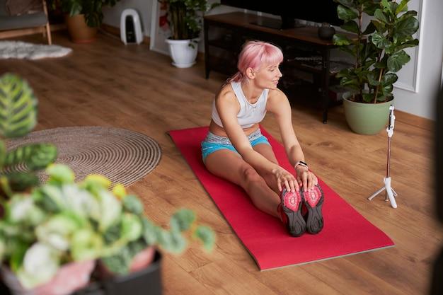 Bloggerin dreht neues video beim vorwärtsbeugen, während sie auf der matte sitzt
