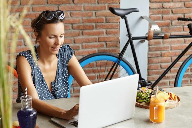 Bloggerin mit stilvoller sonnenbrille auf dem kopf, die einen neuen beitrag über soziale medien schreibt und ein inspiriertes und freudiges lächeln hat