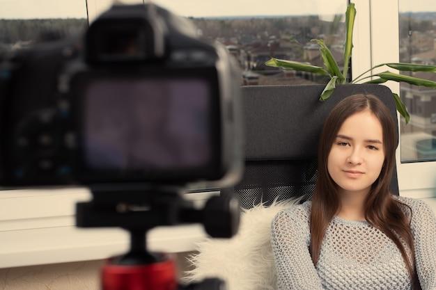 Bloggerin nimmt zu hause ein video auf und sitzt vor der kamera