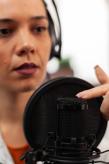 Bloggerin spricht über lifestyle im podcast mit professioneller aufnahmetechnologie im heimstudio. content creator macht neue serien für den kanal und streamt online-sendung auf youtube