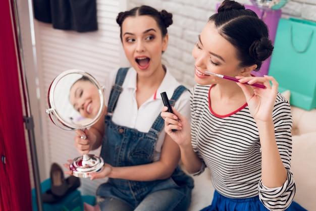 Bloggerinnen halten wimperntusche und spiegel vor die kamera