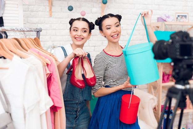 Bloggerinnen präsentieren bunte taschen und rote schuhe.