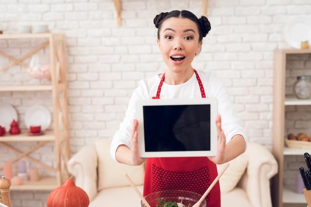 Bloggermädchen hält leere tablette zur kamera