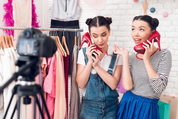 Bloggermädchen präsentieren der kamera buntes kleid und rote schuhe