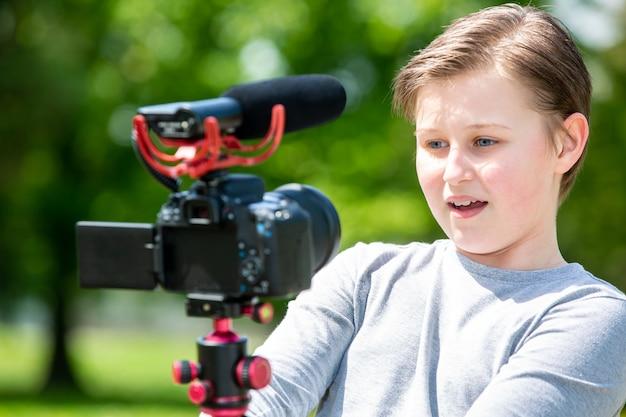 Blogging- und vlogging-konzept, glücklich lächelnder junge oder blogger mit kameraaufzeichnungsvideoblog in außerhalb des waldes