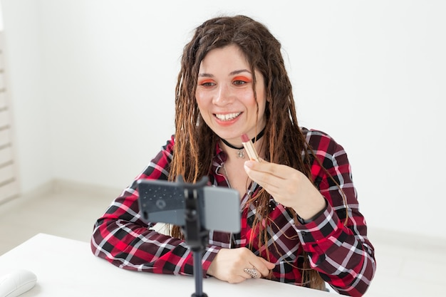Blogging, vlog und people concept - beauty-bloggerin, die ein video über kosmetik macht