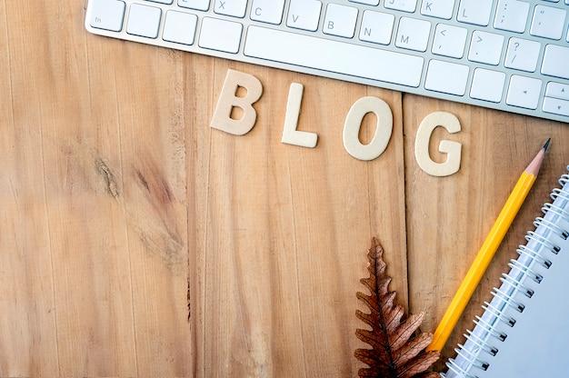 Blogkonzept mit hölzernem arbeitstisch und versorgungen.