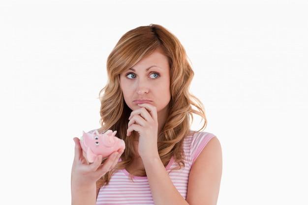 Blond-haarige frau ratlos bezüglich ihres gebrochenen sparschweins