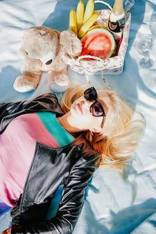 Blond mit langen haaren und einer schwarzen jacke, die auf einer decke am ufer liegt