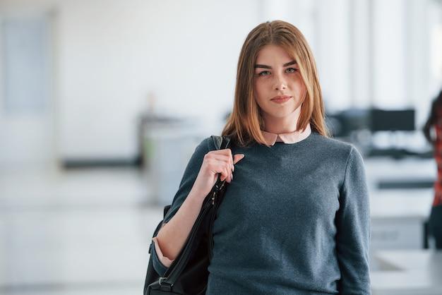 Blond mit schwarzer tasche in den händen. porträt der attraktiven jungen frau, die im büro steht