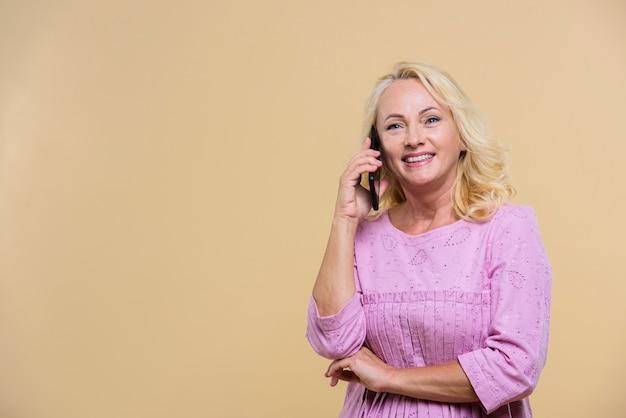 Blonde ältere frau, die am telefon mit kopienraum spricht