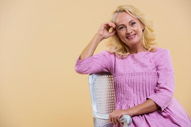 Blonde ältere frau, die ein rosa kleid trägt
