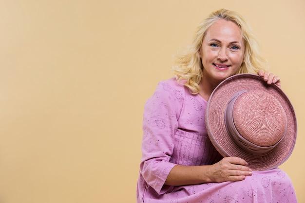 Blonde ältere frau, die einen rosa hut hält
