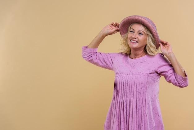 Blonde ältere frau, die einen rosa hut mit kopienraum trägt