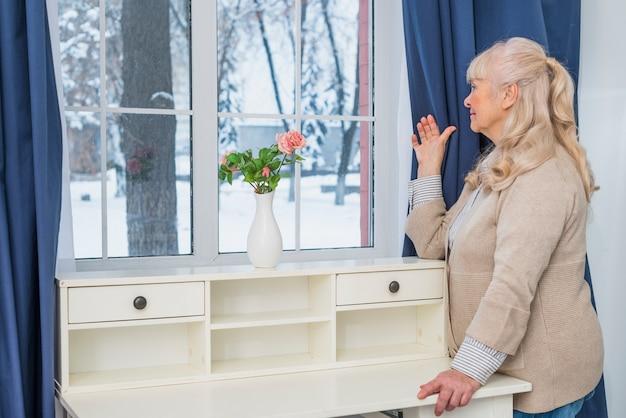 Blonde ältere frau, die zu hause durch fenster schaut