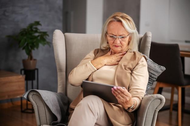 Blonde ältere frau sitzt zu hause, hat gedankenschmerzen und schaut auf tablette, um online-ratschläge zu erhalten.