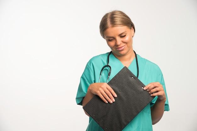Blonde ärztin in blauer uniform, die ein quittungsbuch hält und lächelt.